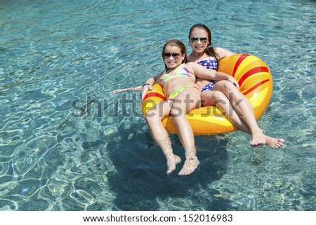 Two girls on float in pool with sunglasses - stock photo