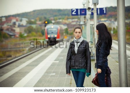 Two girls on railway station - stock photo