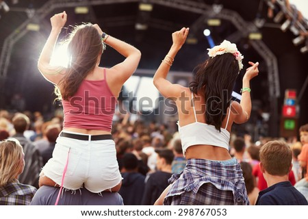 Two girls on shoulders in the crowd at a music festival - stock photo