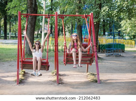 two girls on swing - stock photo