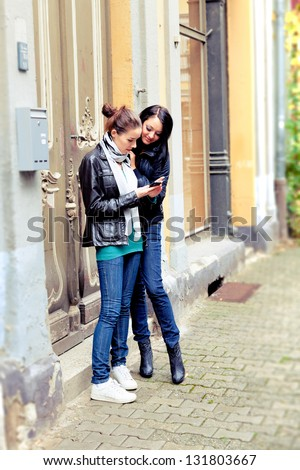 Two girls on the street use a cell phone - stock photo