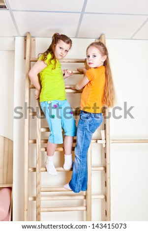 Two girls on the wooden wall bars - stock photo