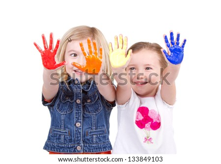 Two girls or children with paint on their hands on an isolated white background - stock photo