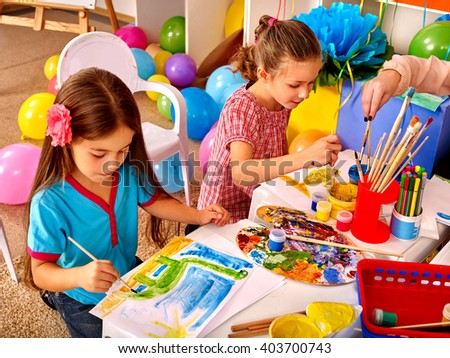 Two girls paint colors. Balloons in the background. - stock photo