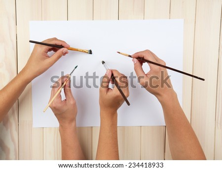 Two girls painting with paintbrush and colorful paints - stock photo