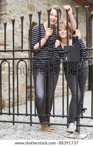 Two girls peeking through closed gate - stock photo