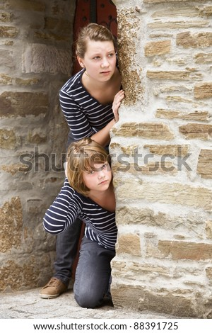 Two girls peeking through the doorway of old church - stock photo