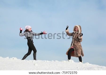 Two girls play snowballs and laugh - stock photo