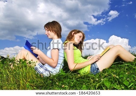 Two girls reading books together outside on grass in summer - stock photo