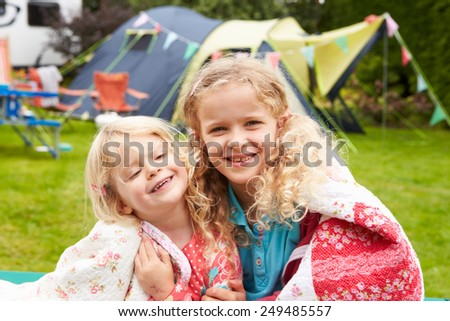 Two Girls Relaxing On Blanket During Family Camping Holiday  - stock photo