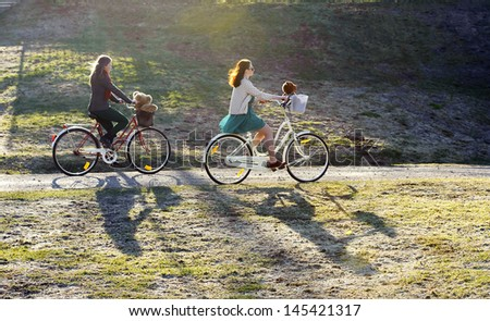 Two girls riding a bike in the park - stock photo