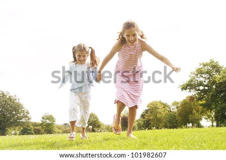 Two girls running towards the camera in the park, smiling. - stock photo