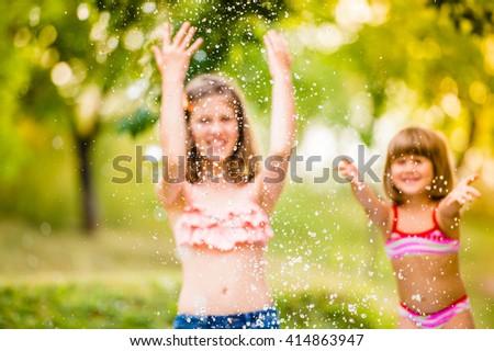 Two girls splashing water, sunny summer in the garden - stock photo