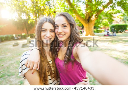 Two girls taking a selfie together at park. They are happy and smiling while looking at camera. Best friends embracing with trees on background. Lifestyle and friendship concepts. - stock photo