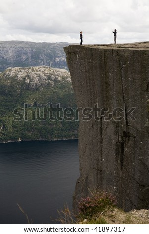 two girls taking pictures on Pulpit Rock above Lysefjord, Norway - stock photo