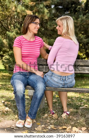 two girls talking on a bench - stock photo