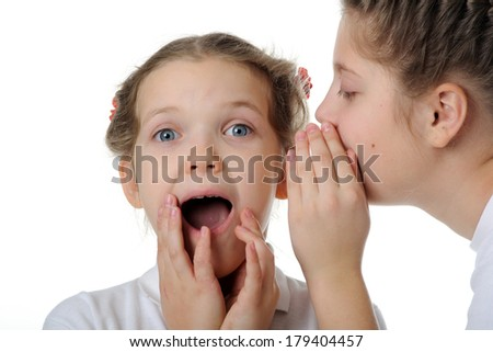 Two girls telling a secret and expressing surprise - stock photo
