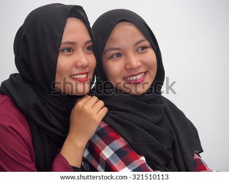 Two girls together looking away.  - stock photo