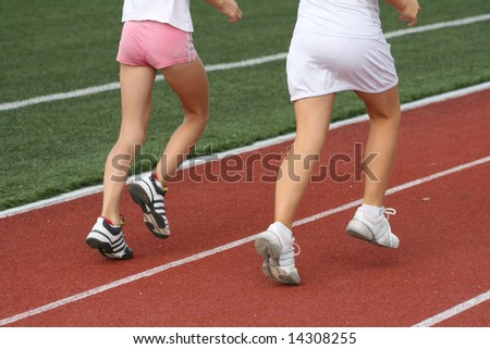 Two girls train in run in stadium - stock photo