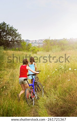 Two girls walking bicycles through rural field in summer - stock photo