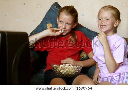 Two girls watching TV - stock photo