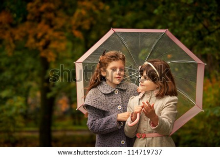 Two girls wearing coats  and felt hats  in autumn park  looking retro style - stock photo