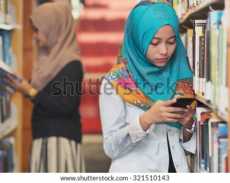 Two girls wearing hijab in a library.       - stock photo