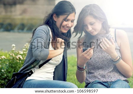 Two Girls While Speaking Looking the cell phone - stock photo