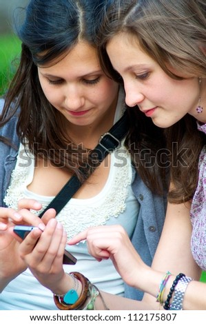 Two Girls while They speak At the Cellular - stock photo