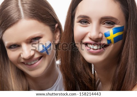 Two girls with painted flags on their face. With flag of Finland and flag of Sweden. Looking at the camera and smile - stock photo