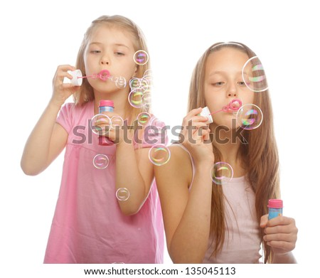 two girls with soap bubbles - stock photo