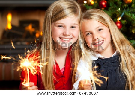two girls with sparklers smiling - stock photo