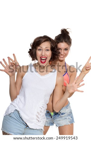 Two girls, young beautiful caucasian female brunette models in shirt, jeans shorts, swimwear posing with expressive emotion, exited, shocked, happy, surprised, wow, showing reaction, isolated on white - stock photo