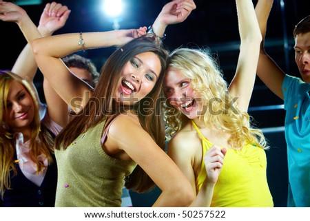 Two glamorous girls enjoying themselves while dancing in night club - stock photo