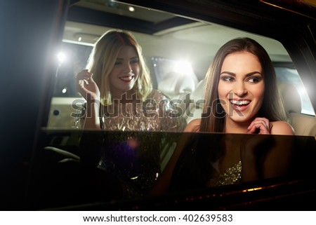 Two glamorous women laughing in the back of a limousine - stock photo