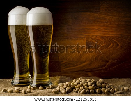 Two glass beer on wood background with copyspace - stock photo