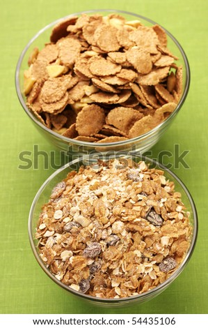 Two glass bowl with breakfast cereal on green cloth. - stock photo