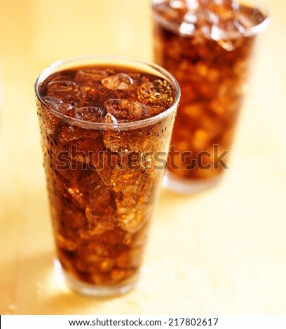 two glass cups of cola soda with ice - stock photo