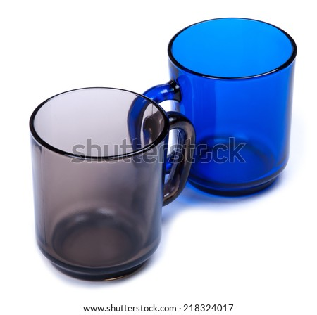 Two glass cups of different colors. Isolated on white background. - stock photo