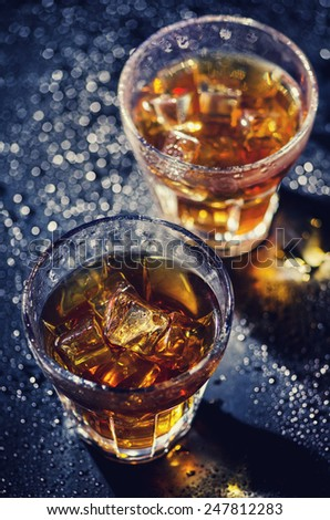 Two glass of iced cocktail on wet background - stock photo