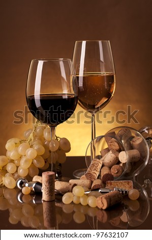 Two glass of red and white wine, and grapes on a golden background. Still-life - stock photo