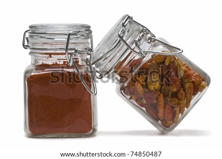 Two glass pots with chiles and paprika isolated on a white background. - stock photo
