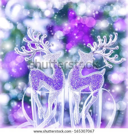 Two glass reindeer ornament on festive blurry background, Christmas tree with purple decoration, wine glasses, New Year greeting card - stock photo
