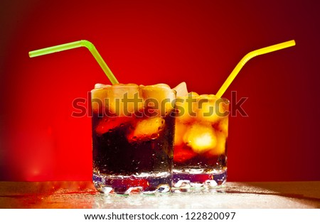 two glass transparent glass with ice cubes and Coke with a green tube on blue background Space for inscriptions - stock photo