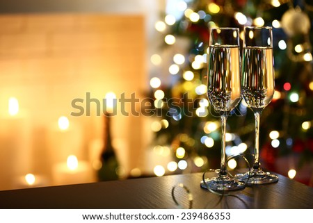 Two glass with champagne on table on Christmas tree and fireplace background - stock photo