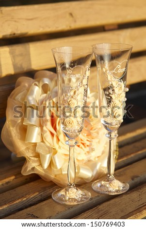 Two glasses and a wedding bouquet on wooden bench at sunset - stock photo