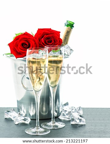 two glasses, bottle of champagne and red roses. festive arrangement with sparkling wine and flowers - stock photo