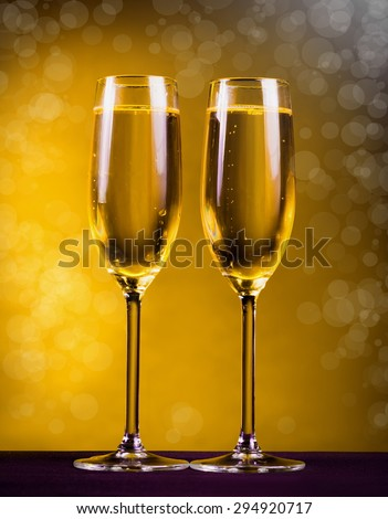 two glasses flutes golden champagne yellow background holiday Christmas new Year Valentine Day event luxury life drink night - stock photo
