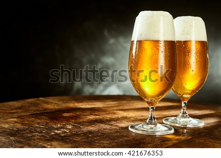 Two glasses full of beer on weathered wooden table with black and gray background - stock photo