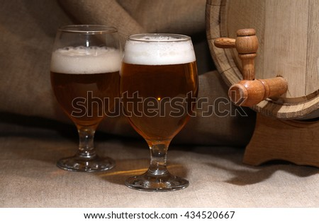 Two glasses full of beer with foam near wooden barrel - stock photo
